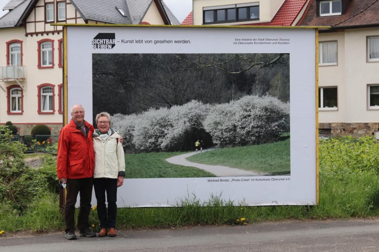 """Winfried Binder (Photo-Circle im Kulturkreis) und seine Frau Gabriele vor seinem Foto """"Im Maasgrund""""."""
