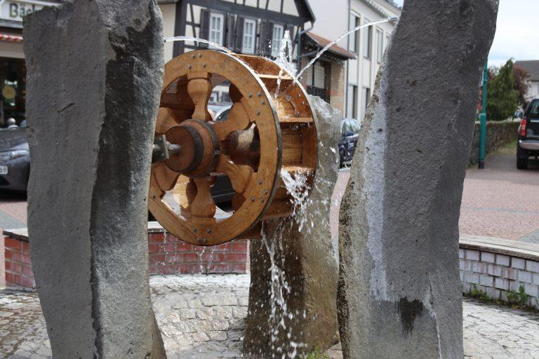 """Der Brunnen mit dem markanten Mühlrad als Assoziation an das """"Mainzer Rad"""" im Wappen des Kurfürstentums Mainz."""