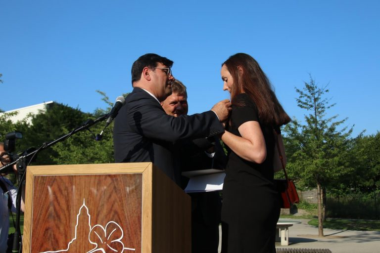 Um ihr die Ehrennadel anzustecken, eilt  jedoch Kreistagsvorsitzenden Renzo Sechi zur Hilfe.