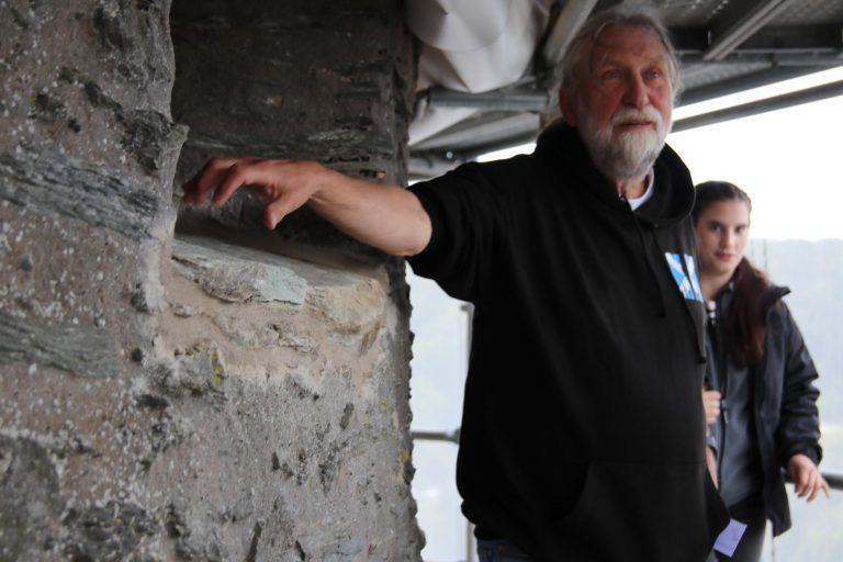 Dr. Joachim Zeune weist auf reparierte Stellen im Mauerwerk hin.