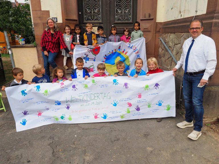 Vorschulkinder zeigten Bürgermeister Patrick Kunkel und der Kinder- und Jugendbeauftragten der Stadt, Ursula Wolf, auf einem selbstgestalteten Plakat, was sie als Kinder glücklich macht. - Foto: Stadt Eltville