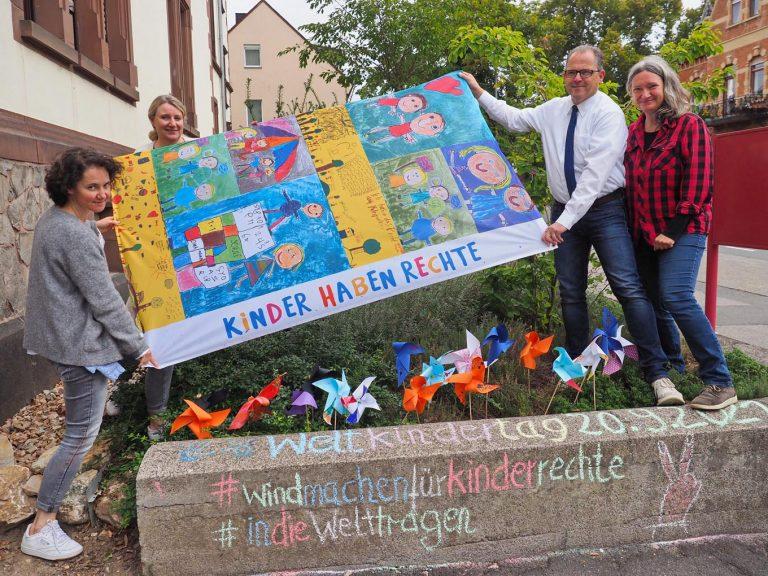 Janina Urbinski (v.l.), Leitung der Kindergartenburg, und ihre Kollegin Monika Knechtel sowie Bürgermeister Kunkel und Kinder- und Jugendbeauftragte Ursula Wolf freuen sich über die Aktion zum Weltkindertag. - Foto: Stadt Eltville